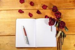 Wysuszone róże z książką i piórem zdjęcie royalty free