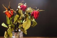 Wysuszone róże w wazie na drewnianym stole na czarnym tle Zdjęcia Stock