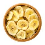 Wysuszony banan szczerbi się w drewnianym pucharze nad bielem Obrazy Royalty Free
