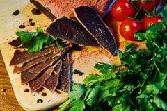 Wysuszony mięso, basturma kłama na drewnianej desce z kaparami i pikantność świeża pietruszka i czerwoni czereśniowi pomidory zdjęcie stock