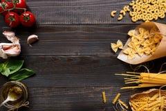 Wysuszony mieszany makaron i warzywa na ciemnym drewnianym stołowym odgórnym widoku fotografia royalty free