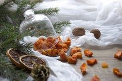 Wysuszony - owocowe dyniowe ananasowe pomarańczowe candied owoc na stole pod szklaną nakrętki nakrętki choinką konusują dokrętki  Obrazy Royalty Free