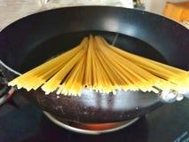 Wysuszony spaghetti jest gotującym czyrakiem w Czarnej niecce fotografia stock