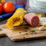 Wysuszony spaghetti makaron z niektóre salami na pomidorach i stronie Obraz Royalty Free