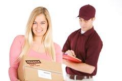 Wysyłać: Kobieta Otrzymywa pakunek Od Doręczeniowego mężczyzna Obrazy Royalty Free