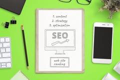 Wyszukiwarki optymalizacji cele kreślą na papierowym i mądrze telefonu mockup na obok zielonego biurowego biurka fotografia royalty free
