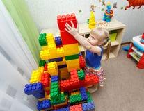 Wytrwała mała dziewczynka buduje duży bloku wierza w daycare Obrazy Stock