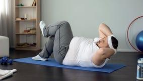 Wytrwały otyły mężczyzna pompuje brzusznych mięśnie robi pokrętnym chrupnięciom, sport obraz stock