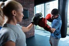 Wytrwały sportowy mężczyzna boksuje mocno w gym fotografia stock