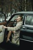 Wywo?awcza dziewczyna w rocznika samochodzie wywoławcza dziewczyna z eleganckim włosy i modnym makeup zdjęcie royalty free