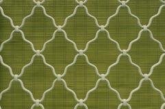 Wzór diamentowy kształt na biel wyginającej się dokonanego żelaza stali na kratownicy okno, zielony bambusowej zasłony tło, roczn zdjęcia royalty free