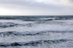Wzór duże fala przy morzem w chmurnym niebie Zdjęcia Royalty Free