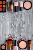 Wzór z oko szminek i cieni beżem, naga postać barwi na popielatym drewnianym tło odgórnego widoku copyspace Zdjęcie Stock