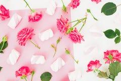 Wzór z różami i marshmallows cukierkiem na tle kwitnie bielu i menchii Mieszkanie nieatutowy, odgórny widok Zdjęcie Royalty Free
