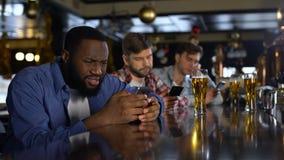 Wzburzeni mężczyźni używa telefony komórkowych w barze, zanudzającym samotnie na weekendach, gadżetu nałóg zbiory