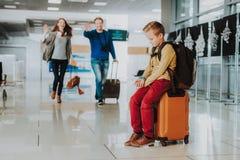 Wzburzona chłopiec czekać na rodziców przy lotniskiem obraz royalty free