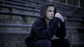 Wzburzona chłopiec czuje depresję, siedzi na stadium trybunie, samotności i stroskaniu, fotografia royalty free