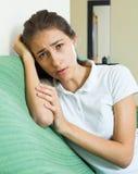 Wzburzona dziewczyna na kanapie w domu Zdjęcie Stock