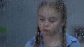 Wzburzona dziewczyna patrzeje w okno na deszczu, cierpiący samotność, czeka wychowywa zbiory wideo
