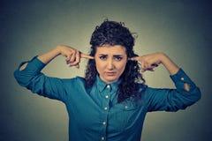 Wzburzona kobieta czopuje ucho z palcami no chce słuchać Fotografia Stock