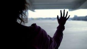 Wzburzona kobieta patrzeje przez lotniskowego okno przy samolotami rodzina, mówić do widzenia obrazy royalty free