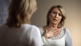 Wzburzona kobieta patrzeje w lustrze i z trudem oddycha, problemy zdrowotni, serce ból zdjęcia stock