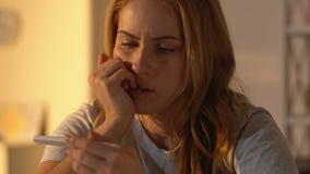Wzburzona kobieta trzyma ciążowego test z negatywnym rezultatem, nieurodzajność problemy zbiory