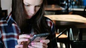 Wzburzona kobieta wysyła wiadomości lub use internet w telefonu obsiadaniu w kawiarni Ubierający w szkockiej kraty koszula zbiory