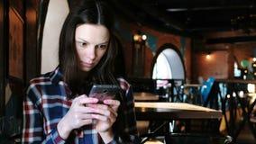 Wzburzona kobieta wysyła wiadomości lub use internet w telefonu obsiadaniu w kawiarni Ubierający w szkockiej kraty koszula zdjęcie wideo