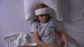Wzburzona kobieta z kompresu lying on the beach w łóżku, cierpienie od migreny bierze pigułkę zbiory