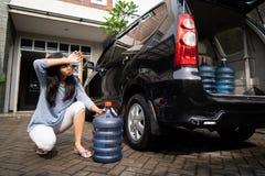 Wzburzona kobiety próba nieść galon woda zdjęcie stock