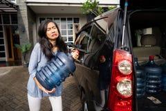 Wzburzona kobiety próba nieść galon woda fotografia stock