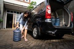 Wzburzona kobiety próba nieść galon woda fotografia royalty free