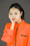Wzburzona młoda Azjatycka kobieta w więźniach munduruje z jej rękami na policzku fotografia stock