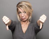 Wzburzona 20s dziewczyna wyraża frustrację z kciukami zestrzela Zdjęcia Royalty Free