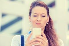 Wzburzona smutna skeptical nieszczęśliwa poważna kobieta opowiada texting na telefonie komórkowym Zdjęcia Stock