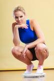 Wzburzona sporty kobieta na ciężar skala Zdjęcia Royalty Free