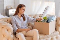 Wzburzonej młodej kobiety siedzący zamyślenie blisko dużego pudełka Obrazy Stock