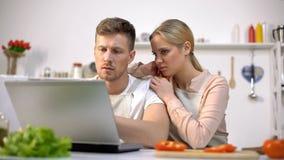 Wzburzonej pary czytelniczy karmowi przepisy na internecie, mieć kłopoty z kucharstwem fotografia royalty free