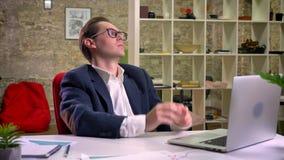 Wzburzony caucasian mężczyzna zatrzymywał jego pracę przy stołem na laptopu patrzeć prosto i główkowaniu, salowi, biurowi klimaty zbiory wideo