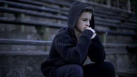 Wzburzony chłopiec obsiadanie na stadium trybunie, odczucie depresji, samotności i stroskaniu, zdjęcia royalty free