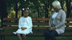 Wzburzony dziewczyny obsiadanie na ławce, babcia próbuje wspierać ona, brak przyjaciele zbiory