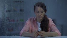 Wzburzony kobiety cierpienie od śmiertelnych choroby mienia pigułek za dżdżystym okno zbiory wideo