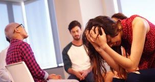 Wzburzony kobiety obsiadanie na krześle z kolegami dyskutuje w tle