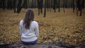 Wzburzony kobiety obsiadanie w jesień parku, melancholiczny sezon, depresja, samotność zdjęcie royalty free