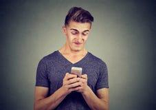 Wzburzony mężczyzna mienia telefon komórkowy obrzydzający z wiadomością otrzymywał fotografia royalty free