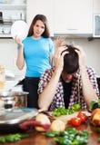 Wzburzony mężczyzna przeciw gniewnej dziewczynie przy kuchnią Obraz Royalty Free