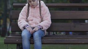 Wzburzony małej dziewczynki obsiadanie na ławce w parku, odczucia osamotneni, brak komunikacja zbiory