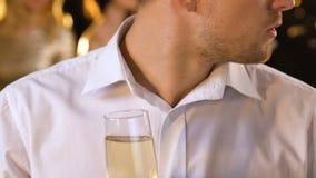 Wzburzony przystojny mężczyzny czuć z zazdrością przy przyjęciem, pić alkohol i patrzeć wokoło, zbiory