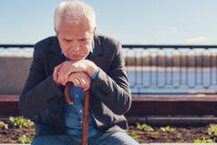 Wzburzony starszy mężczyzna rozpamiętywa podczas gdy siedzący na ławce fotografia stock